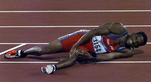 TRINIDAD'S BOLDON HOLDS HIS LEG AFTER THE 200M FINAL IN SYDNEY